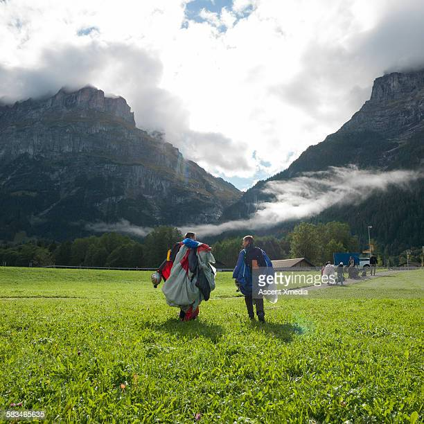 Wingsuit fliers walks across meadow after landing