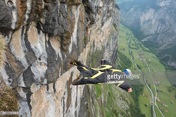 Wingsuit jumper flying along a cliff wall.