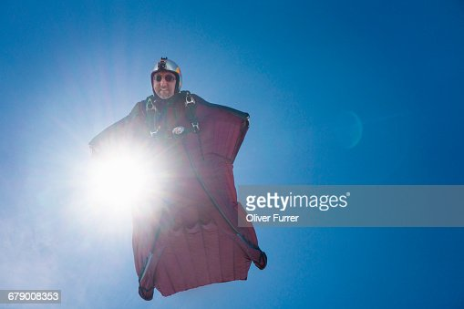 Wingsuit pilot is flying high in the blue sky.