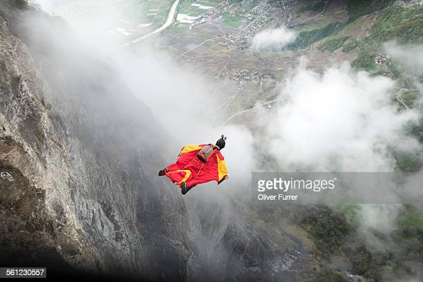 Wingsuit proximity flyer is diving down the cliff