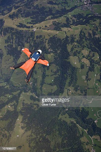 Wingsuit skydiver is tracking over green landscape