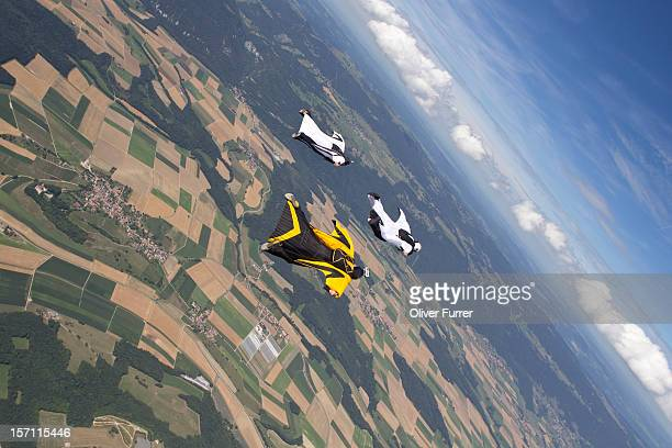 Wingsuit skydivers flying together in the sky