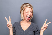 wink and self-confidence concepts - flirting young woman winking and making the v-sign for cool attitude, gray background studio