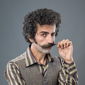 Portrait of mid adult man is winking while curling up his handle bar mustache on gray background.The model has curly hair and looking at the camera.Shot with medium format DSLR camera Hasselblad in st