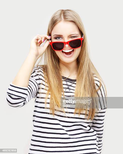 Winking girl  wearing striped top and  red sun glasses
