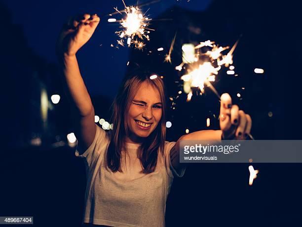 Winking teen Ragazza con sparklers su una strada di notte