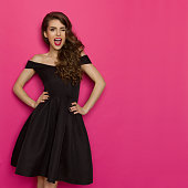 Beautiful young woman in elegant black cocktail dress is holding hands on hip, winking, laughing and looking at camera. Three quarter length studio shot on pink background.