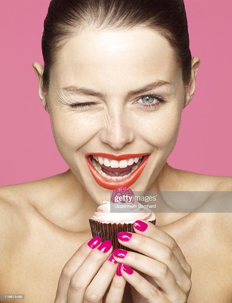 winking young female holding cupcake : Stock Photo