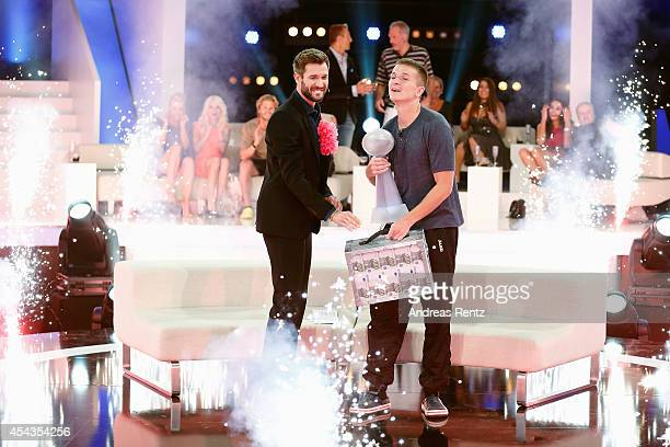 Winner Aaron Troschke reacts next to TV host Jochen Schropp during the Promi Big Brother finals at Coloneum on August 29 2014 in Cologne Germany