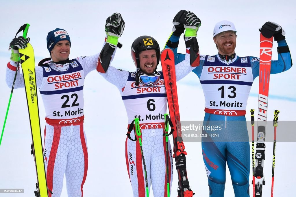 Winner Austria's Marcel Hirscher (C), second-placed Austria's Roland Leitinger (L) and third-placed Norway's Kristian Leif Haugen react in the finish area after the second run of the men's giant slalom race at the 2017 FIS Alpine World Ski Championships in St Moritz on February 17, 2017. / AFP / Fabrice COFFRINI