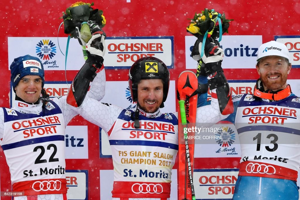 Winner Austria's Marcel Hirscher (C), second-placed Austria's Roland Leitinger (L) and third-placed Norway's Kristian Leif Haugen pose during the flower ceremony of the men's giant slalom race at the 2017 FIS Alpine World Ski Championships in St Moritz on February 17, 2017. / AFP / Fabrice COFFRINI