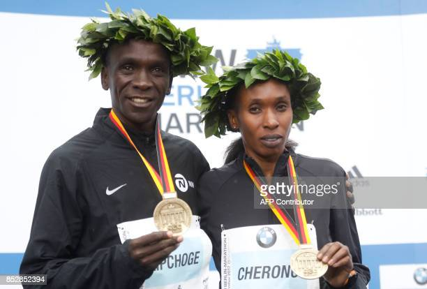 Winner Eliud Kipchoge of Kenya and womens category winner Kenyan Gladys Cherono celebrate with thier gold medals after the Berlin Marathon on...