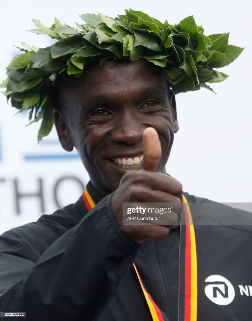 Winner Eliud Kipchoge of Kenya celebrates on the podium after the Berlin Marathon on September 24, 2017 in Berlin. /