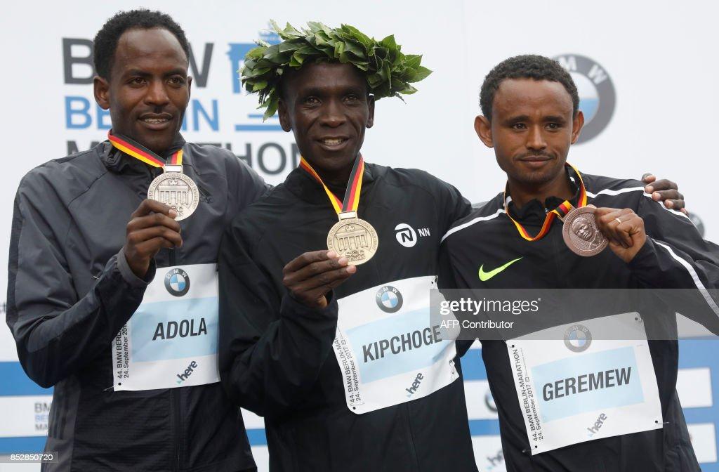 Winner Eliud Kipchoge of Kenya (C), second palced Ethiopian Guye Adola (L) and tird placed Ethiopian Mosinet Geremew celebrate on the podium after the Berlin Marathon on September 24, 2017 in Berlin. /