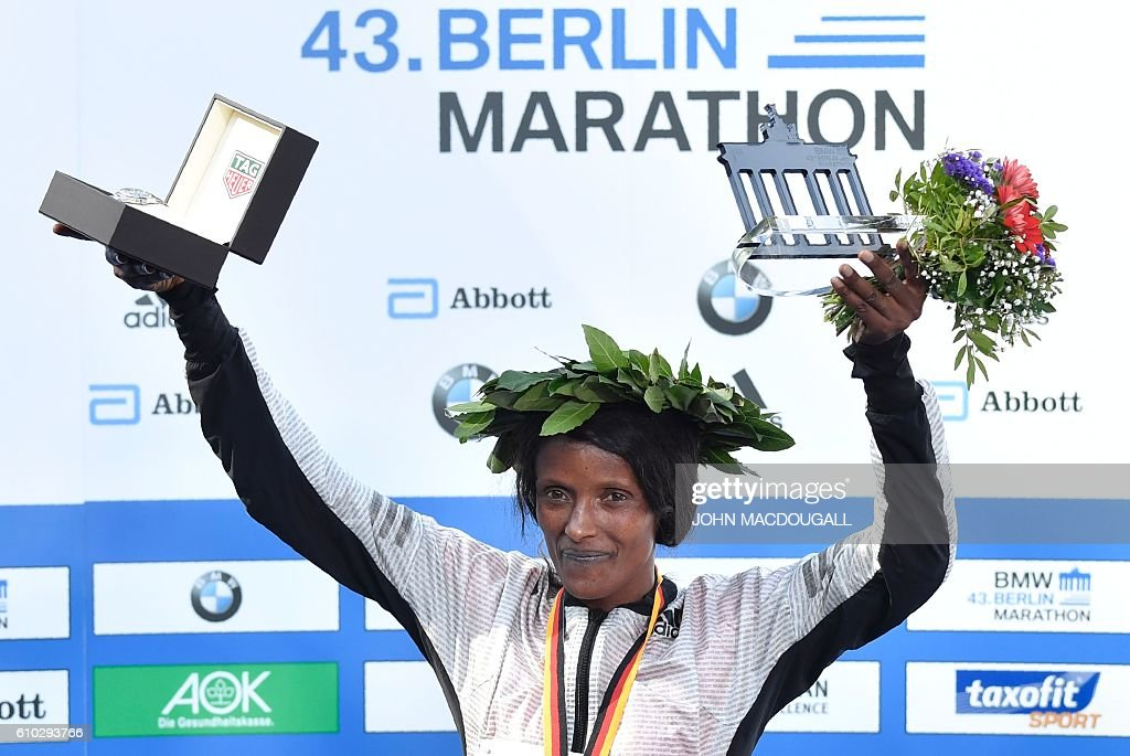 Winner Ethiopian Aberu Kebede poses on the podium with her trophy after winning the women's run of the 43rd Berlin Marathon in Berlin on September 25, 2016. / AFP / John MACDOUGALL