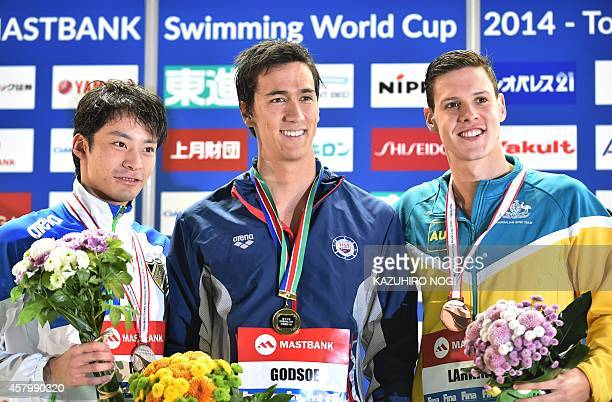 Winner Eugene Godsoe of the US and second place Ryosuke Irie of Japan and third place Michell Larkin of Australia celebrate on the podium during the...