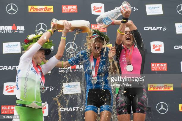 Winner Eva Wutti of Austria second placed Corinne Abraham of Great Britain and third placed Michelle Vesterby of Denmark celebrate after the Ironman...