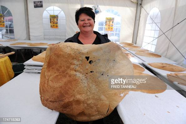 Winner Fabienne Calvez shows the crepe she cooked 84 cm in diameter during the largest crepe of the world contest on July 28 2013 as part of the...