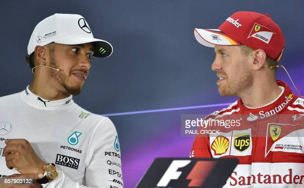 Winner Ferrari's German driver Sebastian Vettel and runnerup Mercedes's British driver Lewis Hamilton take part in a press conference after the...