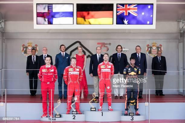 Winner Ferrari's German driver Sebastian Vettel celebrates on the podium next to second placed Ferrari's Finnish driver Kimi Raikkonen and Red Bull's...