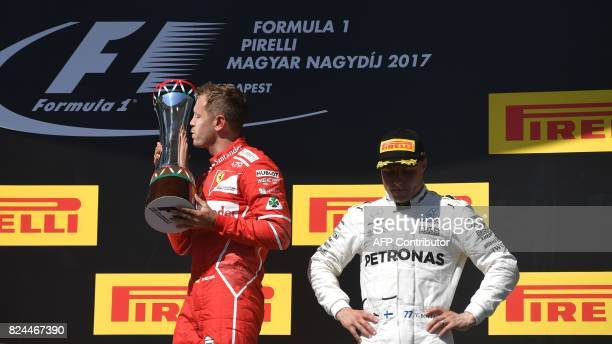 Winner Ferrari's German driver Sebastian Vettel kisses his trophy on the podium at the Hungaroring racing circuit in Budapest on July 30 2017 as 3rd...
