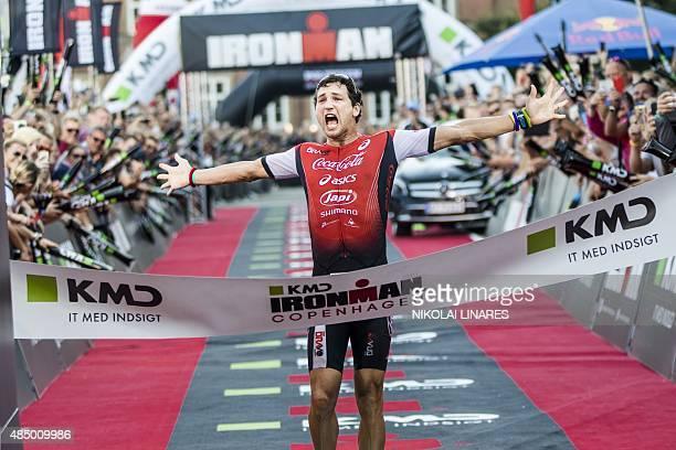Winner Guilherme Valenza from Brazil crosses the finish line of the Ironman Copenhagen 2015 in Copenhagen on August 23 2015 AFP PHOTO / Scanpix...