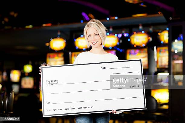 Winner: Happy young woman with blank check in a casino