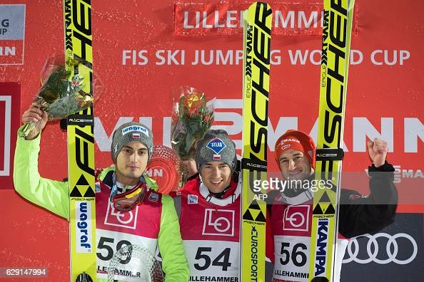 Winner Kamil Stoch of Poland flanked by 2nd placed Maciej Kot of Poland and 3rd placed Markus Eisenbichler of Germany pose at the podium after the...