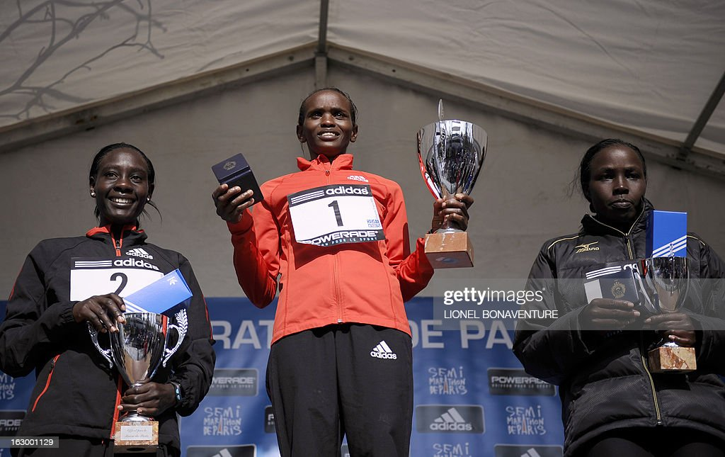 Winner Kenyan athlete Pauline Njeri (C), second placed Kenya's Gladys Kipsoi (L) and third placed Kenya's Monica Jepkoech (R) pose on the podium after winning the 21st edition of the Paris Half-Marathon on March 3, 2013 in Paris.