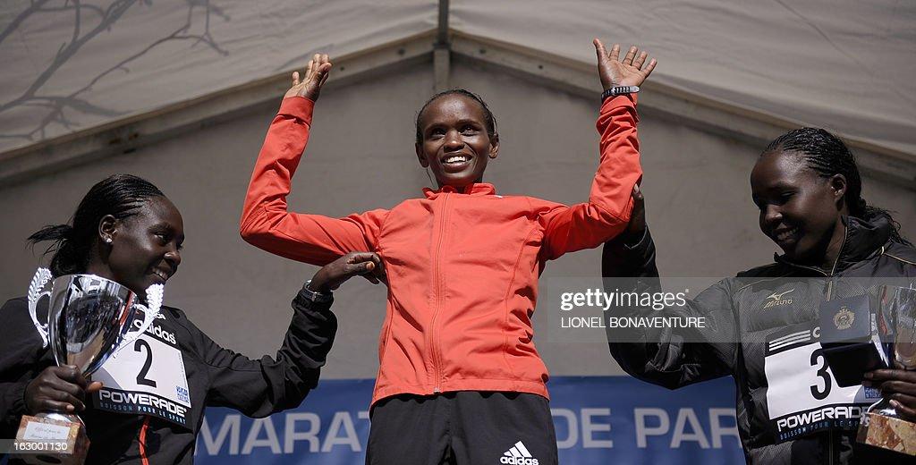 Winner Kenyan athlete Pauline Njeri (C), second placed Kenya's Gladys Kipsoi (L) and third placed Kenya's Monica Jepkoech (R) pose on the podium after winning the 21st edition of the Paris Half-Marathon on March 3, 2013 in Paris. AFP PHOTO / LIONEL BONAVENTURE