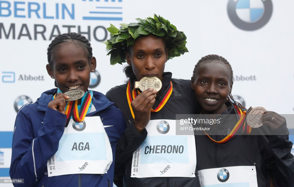 Winner Kenyan Gladys Cherono (C), second placed Ethiopian Ruti Aga (L) and third placed Kenyan Valary Aiyabei celebrate on the podium at the Berlin Marathon on September 24, 2017 in Berlin. /