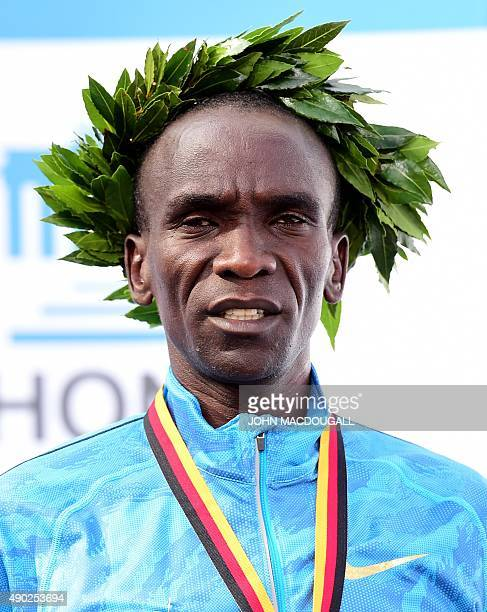 Winner Kenya's Eliud Kipchoge poses on the podium of the 42nd Berlin Marathon on September 27 2015 Eliud Kipchoge failed in his bid to set a third...
