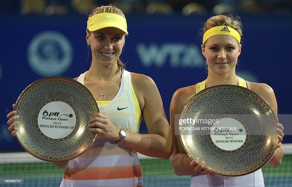 Winner Maria Kirilenko of Russia (R) and runner up Sabine Lisicki of Germany (L) hold their trophies after the tennis women's singles final of the WTA Pattaya Open tennis tournament in Pattaya resort on February 3, 2013. Kirilenko beat Lisicki 7-5, 1-6, 6-7. AFP PHOTO/PORNCHAI KITTIWONGSAKUL
