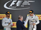 Winner Mercedes AMG Petronas F1 Team's German driver Nico Rosberg is congratulated by Russian President Vladimir Putin as second placed Mercedes AMG...
