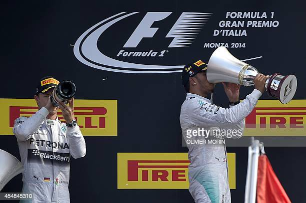 Winner Mercedes' British driver Lewis Hamilton and second placed Mercedes' German driver Nico Rosberg drink champagne with the trophy on the podium...