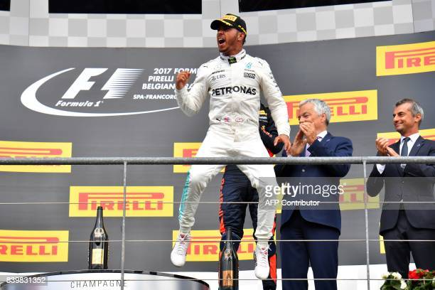 TOPSHOT Winner Mercedes' British driver Lewis Hamilton celebrates on the podium after the Belgian Formula One Grand Prix at the SpaFrancorchamps...