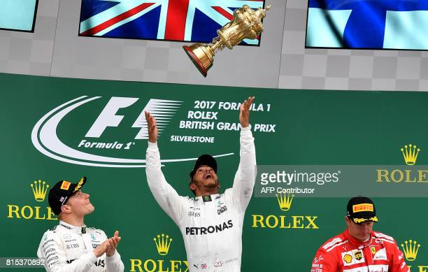 TOPSHOT Winner Mercedes' British driver Lewis Hamilton celebrates with his trophy on the podium next to second placed Mercedes' Finnish driver...