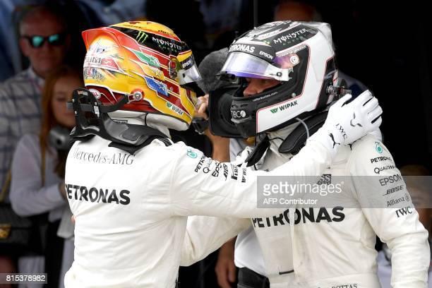 Winner Mercedes' British driver Lewis Hamilton is congratulated by teammate Mercedes' Finnish driver Valtteri Bottas after the British Formula One...