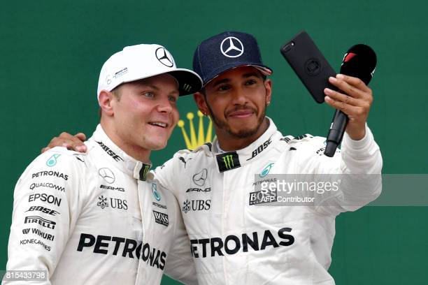 Winner Mercedes' British driver Lewis Hamilton poses for a selfie with second placed Mercedes' Finnish driver Valtteri Bottas after the British...
