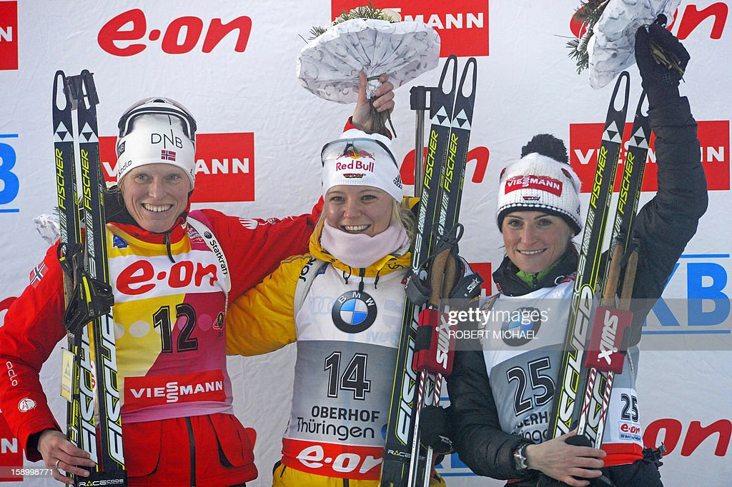 Winner Miriam Goessner (C) of Germany, the second placed Tora Berger of Norway (L) and the third placed Andrea Henkel of Germany celebrate on the podium after the women's 7,5 km sprint event of the IBU biathlon World Cup in the eastern German town of Oberhof on January 5, 2013.