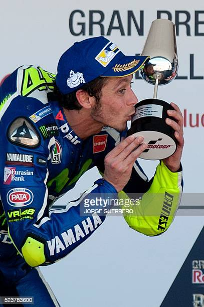 Winner Movistar Yamaha MotoGP's Italian rider Valentino Rossi kisses his trophy on the podium of the MotoGP race of the Spanish Moto Grand Prix at...