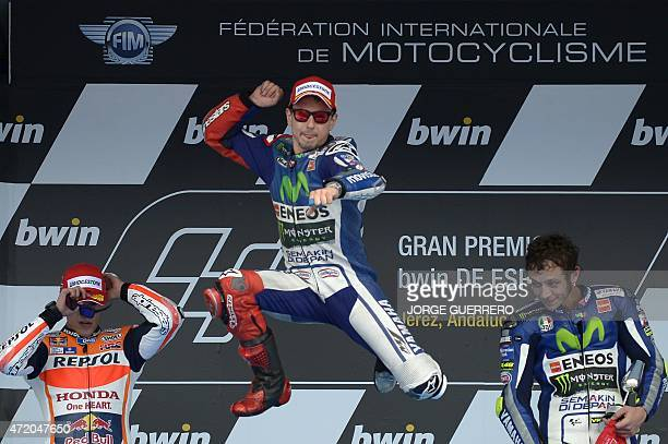Winner Movistar Yamaha MotoGP's Spanish rider Jorge Lorenzo jumps flanked by second Repsol Honda Team's Spanish rider Marc Marquez and third Movistar...