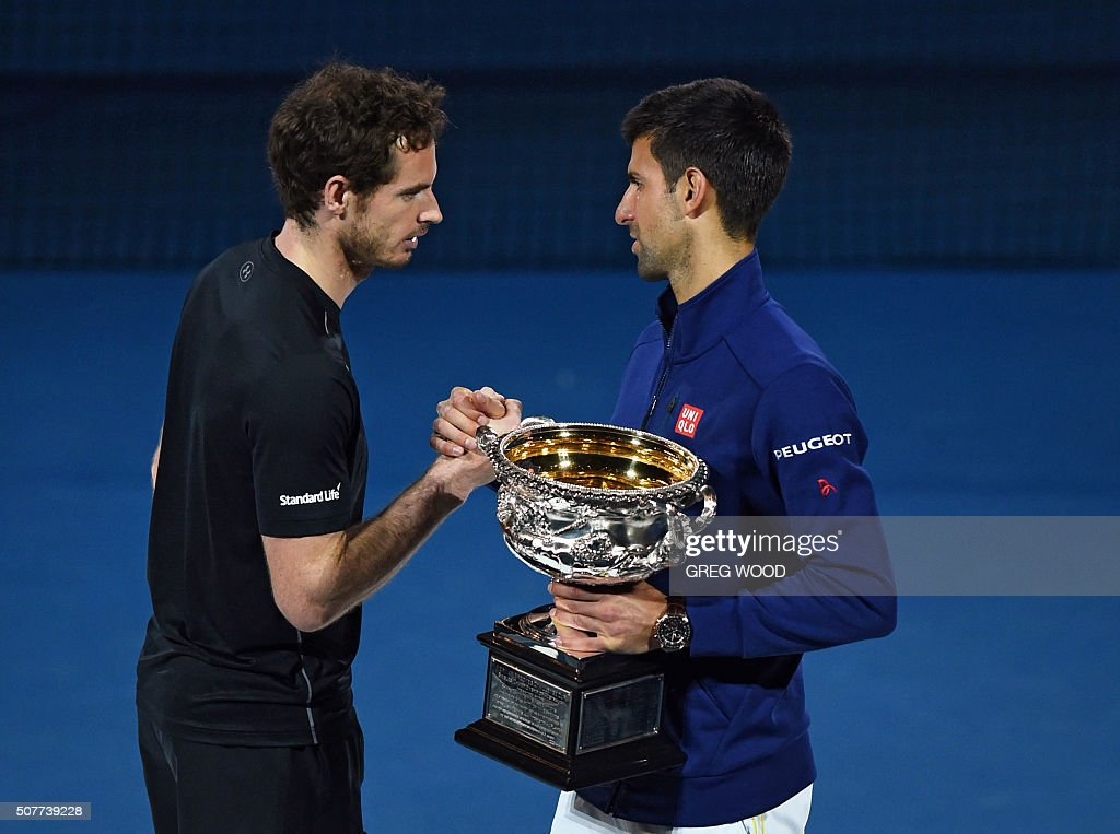 Winner Novak Djokovic of Serbia (R) holds the winner's trophy as he shakes hands with runner-up Andy Murray of Britain (L) at the awards ceremony after their men's singles final match on day 14 of the 2016 Australian Open tennis tournament in Melbourne on January 31, 2016.