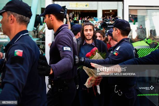 Winner of 2017 Eurovision contest Salvador Sobral escorted by policemen smiles upon his arrival at Humberto Delgado Lisbon's airport on May 14 2017 /...