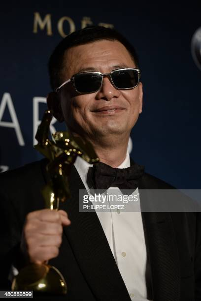 Winner of best film and best director Hong Kong filmmaker Wong Karwai poses during the Asian Film Awards in Macau on March 27 2014 Movie stars...