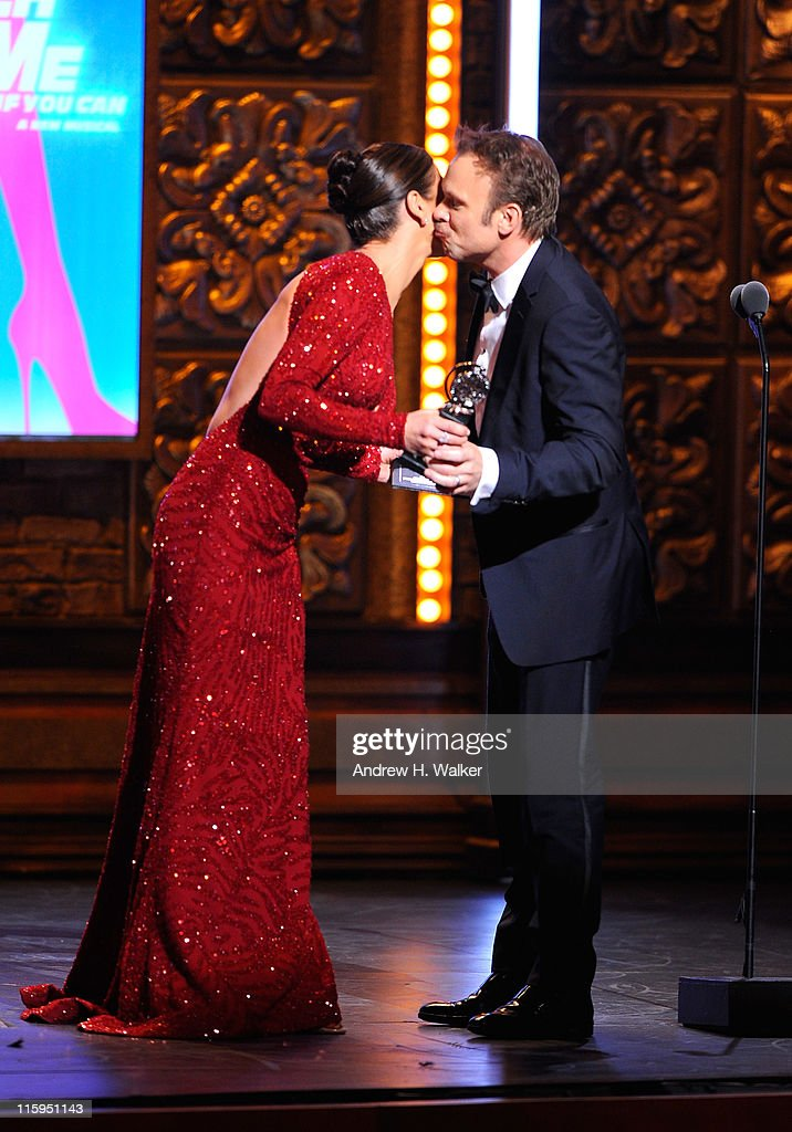Winner of Best Performance by an Actor in a Leading Role in a Musical Norbert Leo Butz accepts his award from Catherine Zeta-Jones on stage during the 65th Annual Tony Awards at the Beacon Theatre on June 12, 2011 in New York City.