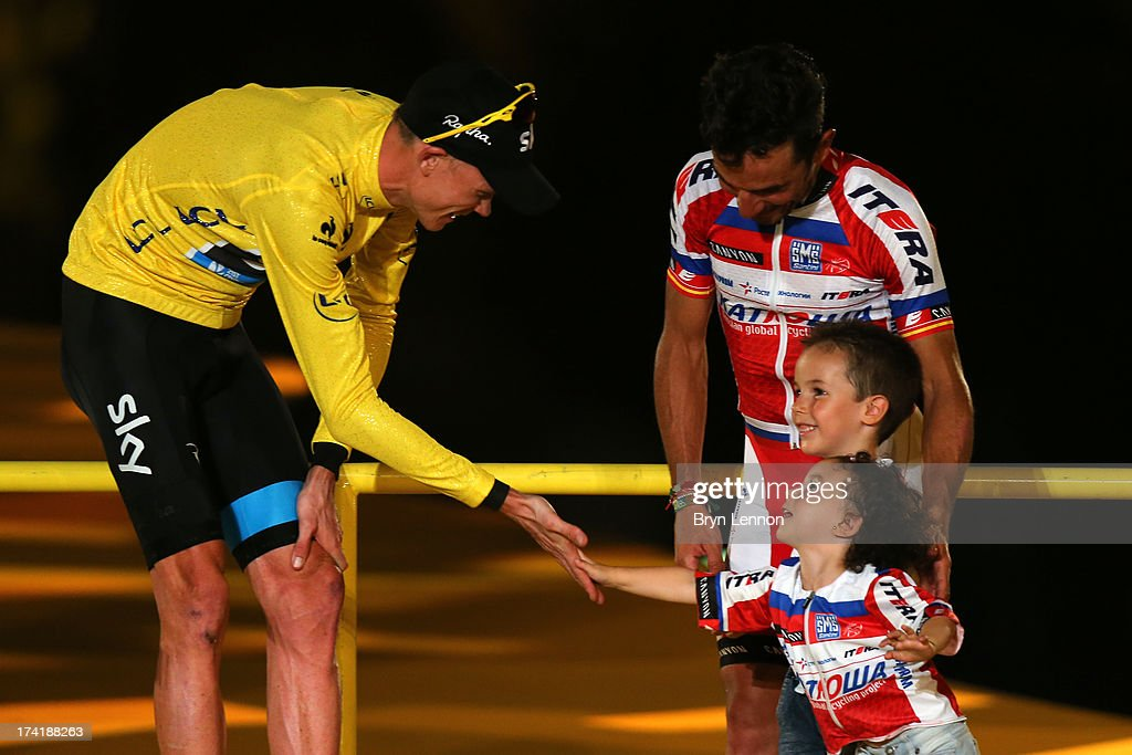 Winner of the 2013 Tour de France, Chris Froome of Great Britain and SKY Procycling shares a joke with the children of third placed Joaquin 'Purito' Rodriguez of Spain and Team Katusha on the podium after the twenty first and final stage of the 2013 Tour de France, a processional 133.5KM road stage ending in an evening race around the Champs-Elysees, on July 21, 2013 in Paris, France.