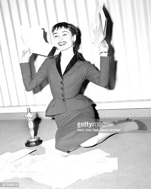 Winner of the best actress award for her role in 'Roman Holiday' vivacious Audrey Hepburn has a holiday herself as she reads congratulatory telegrams...