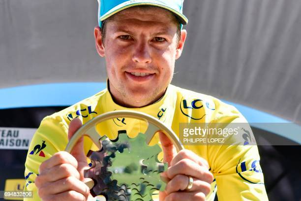 Winner of the Criterium du Dauphine 2017 Denmark's Jakob Fuglsang poses with his trophy as he celebrates his overall leader yellow jersey on the...