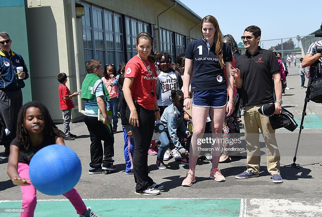 Winner of the Laureus World Sports Award for a female athlete and four-time Olympic gold medalist Missy Franklin standing with Nathaniel Foster (Executive Director), right, and Elena Turanin (coach), left, of Playworks watches students from Bayview Elementary School play foursquare during Franklin's visit to the school on June 3, 2014 in San Pablo, California.